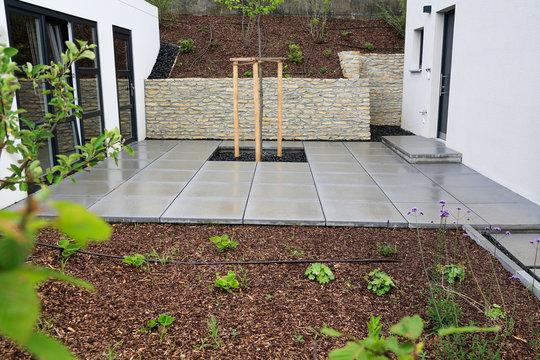 Moderner Gartenbau und Terrassengestaltung eines Neubaus an einem Hanggrundstück im Materialmix: Mauer aus Natursteinen, Pflastersteine aus Beton, Pflanzen und Bäume umgeben von Mulch und Schotter