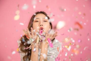 Foto op Textielframe Carnaval Portrait of a cheerful beautiful Asian womanl wearing dress standing standing under confetti rain and celebrating isolated over pink background.She blowing confetti from her hands .