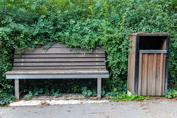 An empty wooden bench with a waste bin beside way with the green bush around.