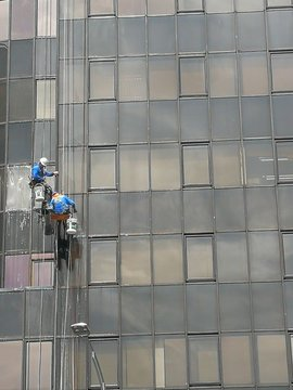 Men working at heights, cleaning building exterior.