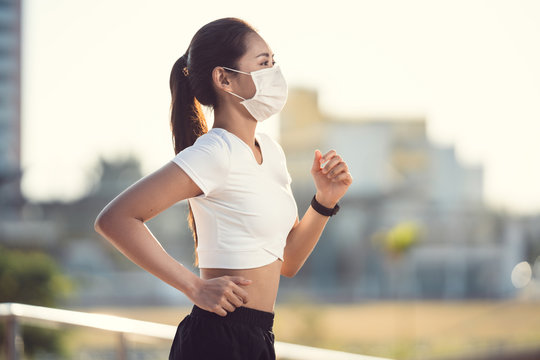 Woman runners morning exercise she wears a nose mask. Protection against dust and viruses