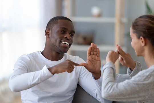 Smiling African American man and woman speaking sign language