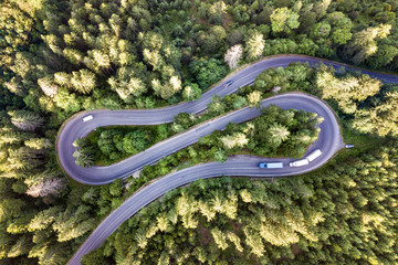 Poster de jardin Route dans la forêt Aerial view of winding road in high mountain pass trough dense green pine woods.