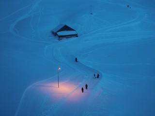 strolling people at dusk on snowy landscape Fotobehang