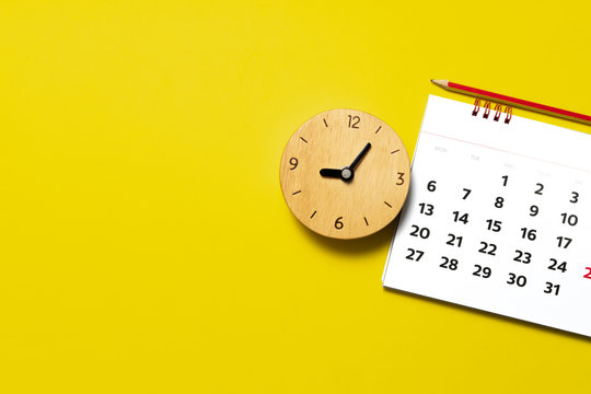 close up of calendar and alarm clock on the yellow table, planning for business meeting or travel planning concept