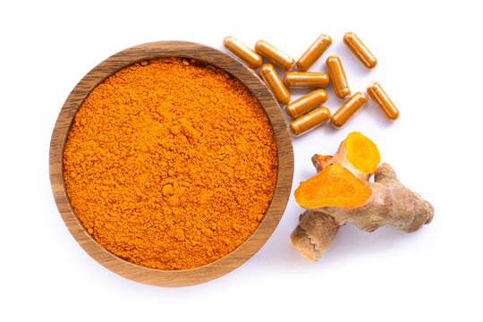 Turmeric ( curcumin, Curcuma longa Linn) powder in wooden bowl and tumeric capsule with rhizome and sliced isolated on white background. Supplement concept. Top view. Flat lay.Copy space for text.