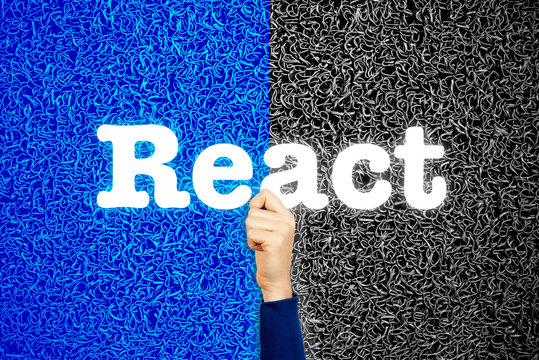 React front end programming language concept. Woman developer with her hand holding modern sign with word react, on wire background.