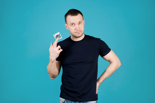 Athletic young man with stubble holds a condom in his hand and looks straight