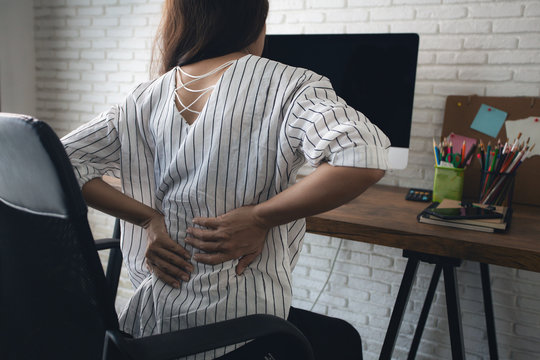 Business woman suffering from back pain in office