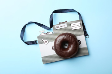 Camera made from donut and piece of cardboard on light blue background, top view