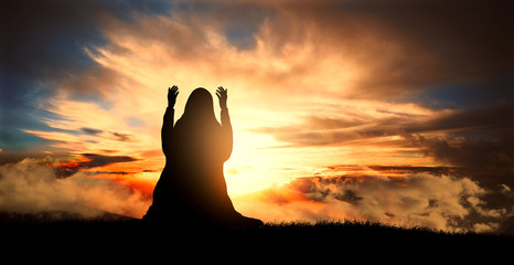 silhouette of a Muslim woman praying at sunset