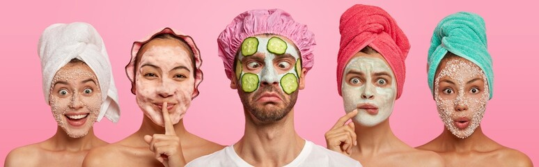 Funny crazy man crosses eyes, applies slices of cucumbers and clay mask, wears bath hat, stands...