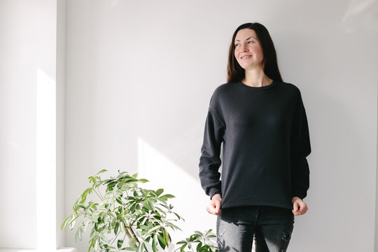 Woman wearing black sweatshirt standing over white wall background. Sweatshirt or hoodie for mock up, logo designs or design prints with with free space