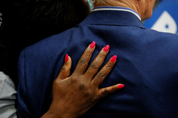 A woman puts her hand on the back of Democratic U.S. presidential candidate and former U.S. Vice President Joe Biden while posing for a photo at Saint Augustine's University in Raleigh
