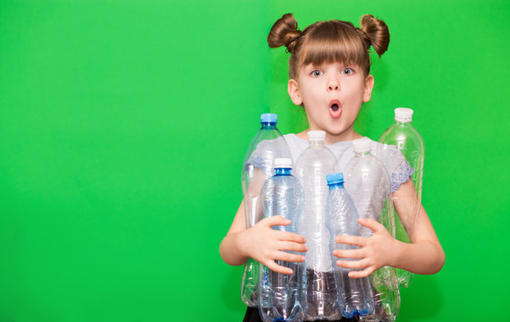Photo of confused funny little girl holding plastic bottles and looking at camera isolated over green background