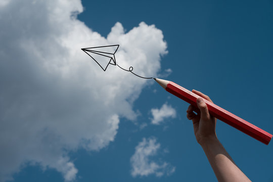 Hand drawing a plane in the blue sky