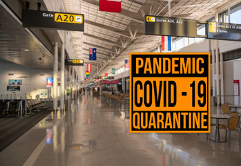 Pandemic sign warning of quarantine due to Covid-19 or corona virus in the USA against background of empty airport terminal