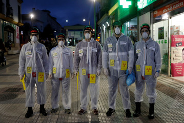 Carnival revellers dressed up as doctors in protective suits to avoid contracting coronavirus, pose for a photo during the carnival in Ronda