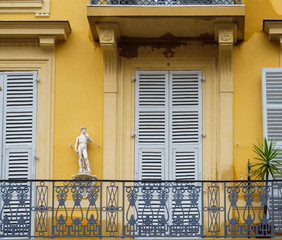 View from the street of large balcony painted in yellow with antique statue and closed window shutters
