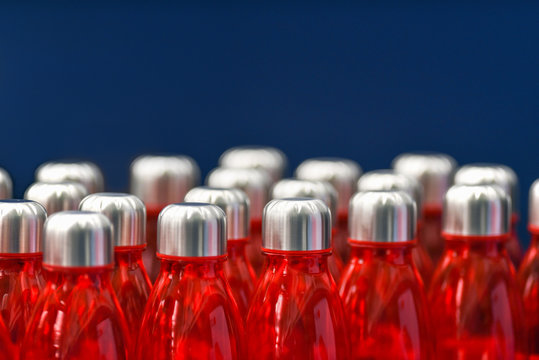 Red water bottles with silver metallic caps in rows isolated on blue background