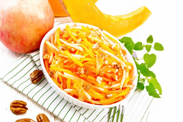 Wall Mural - Salad of pumpkin and apple with nuts in bowl on white board