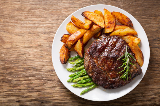 plate of grilled steak with rosemary, asparagus and potato, top view