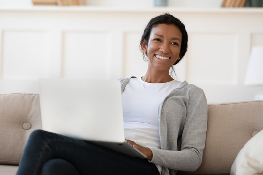 Smiling biracial woman distracted from computer talking with someone