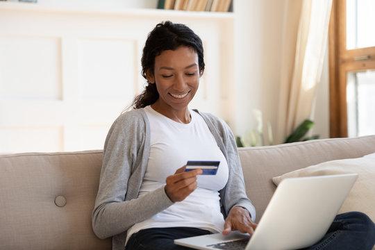 Happy biracial woman shopping online using laptop