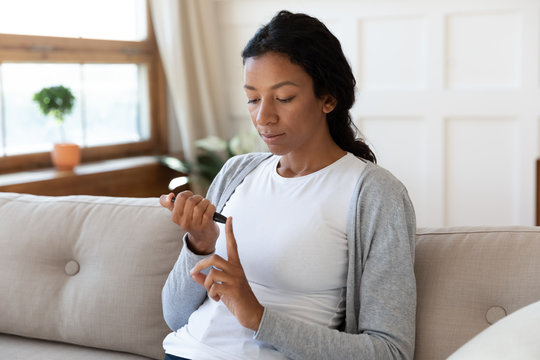 African American woman measure blood sugar level at home