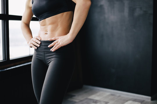 Fitness, sport and active lifestyle. Motivation. Intensive work out. Sweaty muscular body of sporty woman, copy space