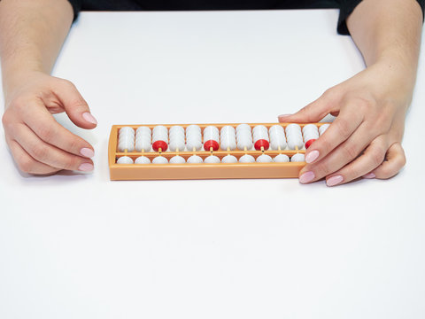 Classes in mental arithmetic, hands and abacus soroban on white background. closeup. copy space
