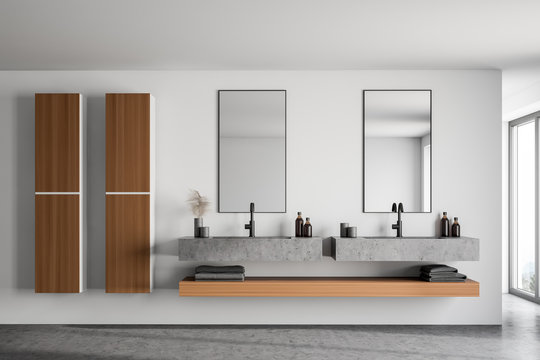 Double sink and cabinets in white bathroom