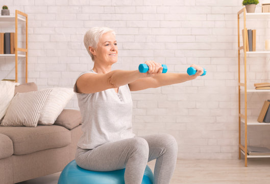 Senior woman in sportswear exercising with dumbbells at home