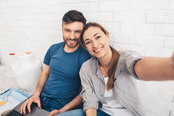 Happy young couple sitting in new apartments