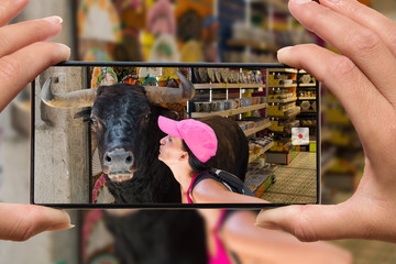 Photographing on cell phone women kissing bull on vacation in Spain.
