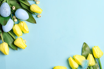 Corner festive frame from handmade blue painted eggs and fresh flowers on a blue background.
