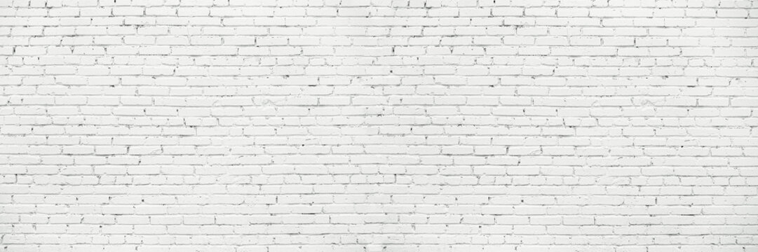 White Long Wide Wall Textured Background. Whitewashed Brick Facade Of Grungy Shabby Uneven Painted Plastered Wall. Whitened Brick Face Of Fence.