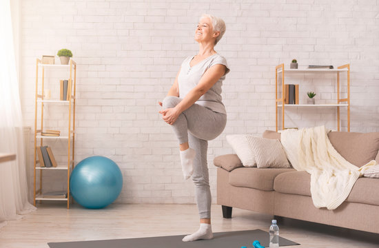Active senior woman doing legs exercise at home