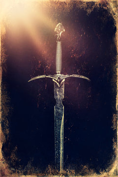 Magyc sword on moss background, old photo effect.