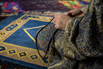 Muslim woman praying for Allah muslim god at room near window. Hands of muslim woman on the carpet praying in traditional wearing clothes, Woman in Hijab, Carpet of Kaaba, Selective focus, toned
