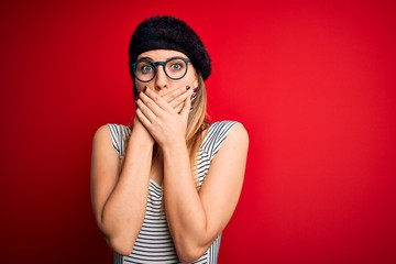 Beautiful blonde woman with blue eyes wearing french beret and glasses over red background shocked covering mouth with hands for mistake. Secret concept. Fotobehang