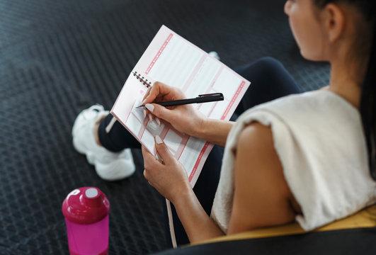 Young woman making her workout schedule in notebook indoors, above view