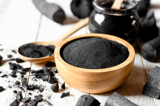 Black charcoal powder for facial mask and scrub, placed on a white wooden table, health and beauty concept.