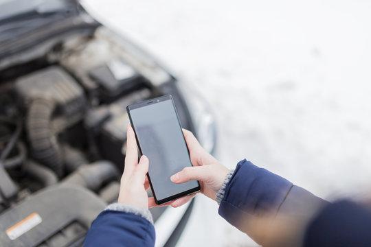 Close up of female holding blank screen smart phone against broken car. Winter scene.