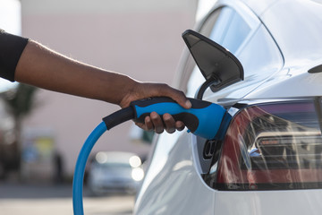 African American person plugin her EV electric car at the charging station