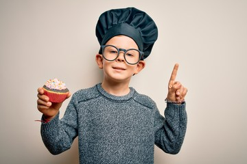 Young little caucasian cook kid wearing chef uniform and hat cooking cupcake surprised with an idea or question pointing finger with happy face, number one