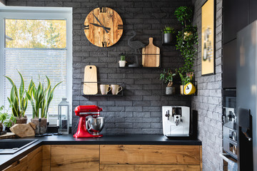 Wooden clock on black brick wall in trendy kitchen with red kitchen robot