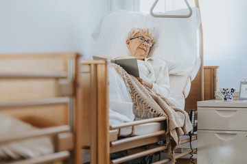 Sick senior woman lies in a hospital bed and reads a book