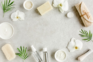 Photo sur Toile Spa Spa skincare concept. Natural/Organic spa cosmetics products, sea salt and tropic palm leaves on gray marble table from above. Spa background with a space for a text, flat lay, top view.