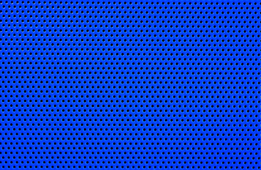 Macro of a blue plastic surface, with regular geometrically arranged round holes. Abstract blue background.